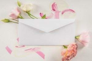 Envelope sitting on pink and white flowers.