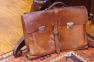 Worn leather bag on a area rug.