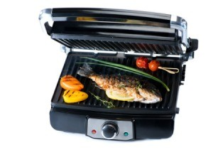 Electric tabletop grill with fish and veggies.