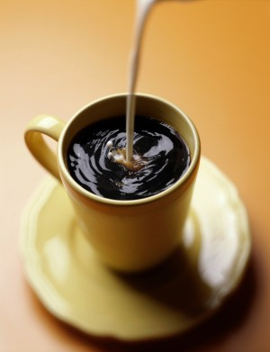 Coffee creamer being added to a cup of coffee.