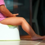 A toddler sitting on a plastic portable potty.