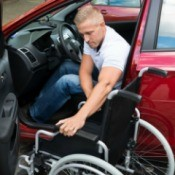 A disabled man moving from his car into a wheelchair.