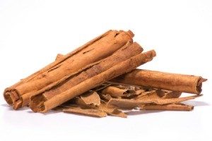 A pile of cinnamon sticks on a white background.