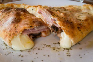 A ham and cheese calzone with melted cheese.