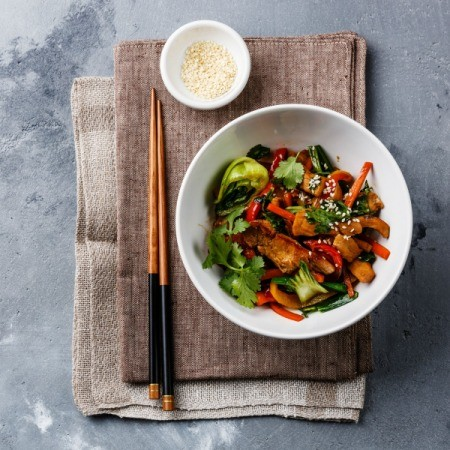A bowl of stir fry chicken and vegetables with sesame seeds.