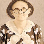 A sepia toned photo of an old fashioned woman with round glasses.