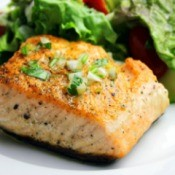 Salmon with fresh greens on a white plate.