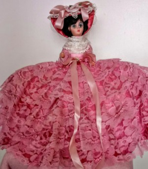 Identifying and Value of  a Vintage Doll - small plastic doll wearing a ruffled dark pink dress and hat