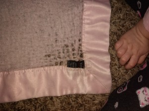 A pink cashmere baby blanket with satin trim, with some brown staining.