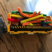 A toy train with cargo of colored pipe cleaners.
