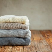 Stack of sweaters on a wood floor.