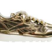Gold patent leather sneaker on a white background.