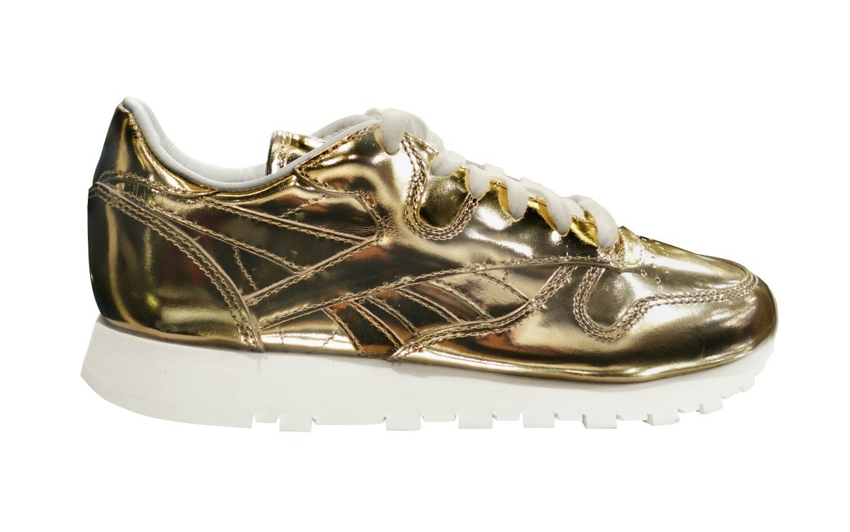 0d764812e613 Gold patent leather sneaker on a white background.