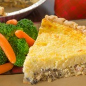 A slice crabmeat pie with a side of steamed broccoli and carrots.