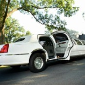 White limo parked on a tree lined street with the back door opened.