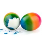 Two rainbow dyed easter eggs, one partly peeled.