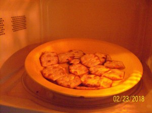 A plate of crackers in the microwave becoming crispy.