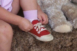 Little girl tying her red shoes