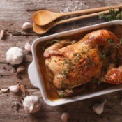 Whole roasted chicken in a pan surrounded with garlic.