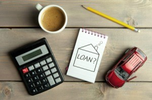 "Calculator, cup of coffee, pencil, toy car and a notepad with ""Loans?"" written on it."