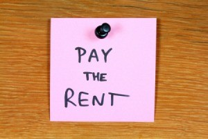 "Postit note, with words ""Pay the Rent"" written on it."