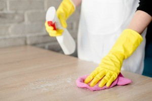 Hands wearing yellow rubber gloves cleaning a laminate tabletop.