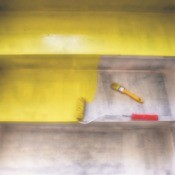 Paint roller and brush on half painted yellow cement stairs.