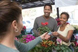Couple at farmers market purchasing flowers with a debit card.