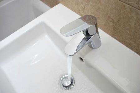 Faucet running water into Bathroom Sink
