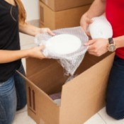 Couple packing dishes wrapped in bubble wrap into a box.