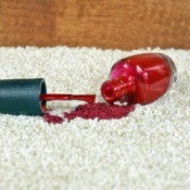 Bottle of red nail polish spilling on a beige carpet.