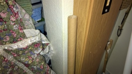 A cardboard tube being used to extend a broom handle.
