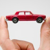 Hand holding a small red matchbox car.