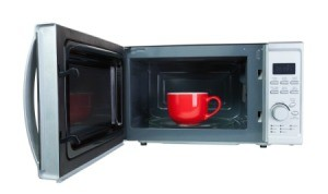 Red mug inside an open microwave.