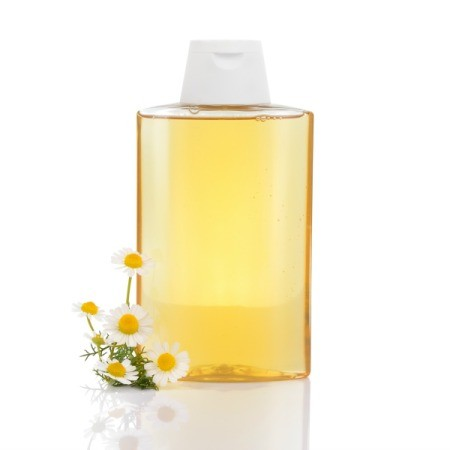 Bottle of shampoo with chamomile flowers.