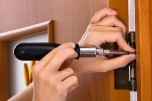 Hand removing a screw from a door hinge.