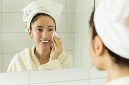 Woman looking in the mirror with a towel on her head using a cotton pad on her face.