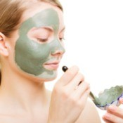 Woman applying green facial mask with a brush.