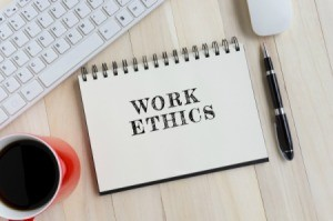 "Keyboard, mug of coffee, pen and a notebook with the words ""Work Ethics"" printed on it."