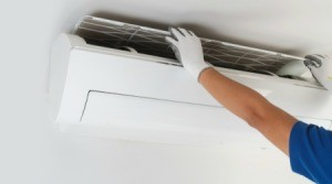Person lifting off the ac filter on a wall air conditioning unit.