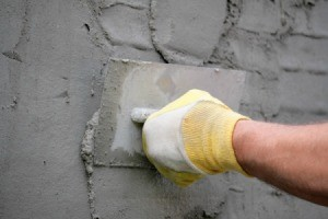 Person applying Stucco to a wall.