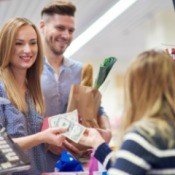 Woman paying grocer with cash
