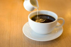 Cream being poured into a cup of coffee.