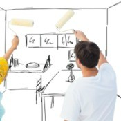 Man and woman with paint rollers pretending to paint a drawing of a room.