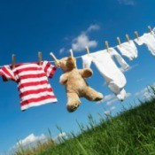 Clothes and a teddybear drying on the line on a clear day.