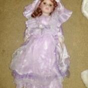 Identifying and Determining Value of Porcelain Dolls - red haired doll wearing a lavender dress