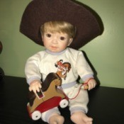 Value of Porcelain Dolls - boy child doll wearing a very large cowboy hat