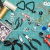 Earring making supplies spread out on a green mat.