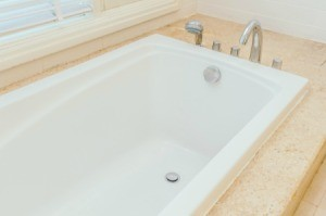 Clean white built in bathtub surrounded by sand colored tiles.