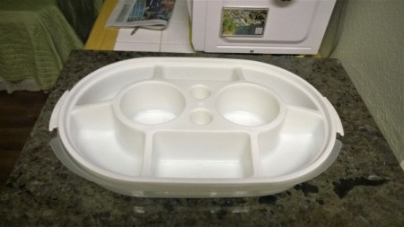 An old empty Tupperware container with several sections.